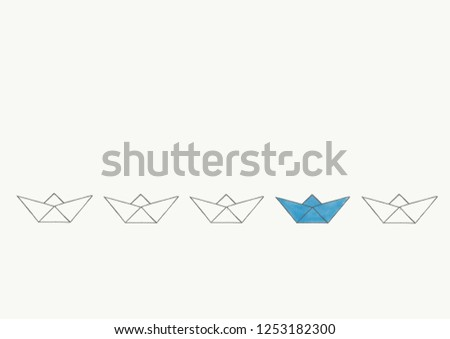 folded paper ships, boats in a row. One is different, blue than the others #1253182300