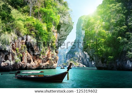 long boat and rocks on railay beach in Krabi, Thailand Royalty-Free Stock Photo #125319602