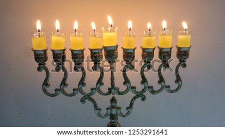 Vintage oil chanukiah - traditional Jewish candelabrum with nine candles burning during the holiday of Chanukah. Hanukkah, Hanukah concept image.