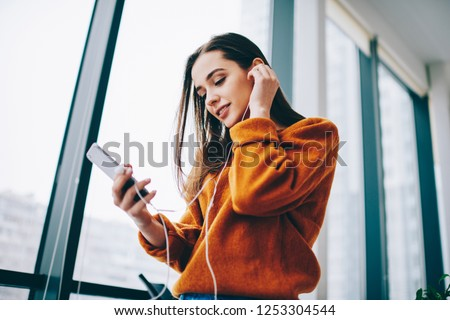 Young female teenager enjoying favourite music playlist listening via application on cellular gadget and electronic earphones, hipster girl spending time for audio book while installing new media app #1253304544