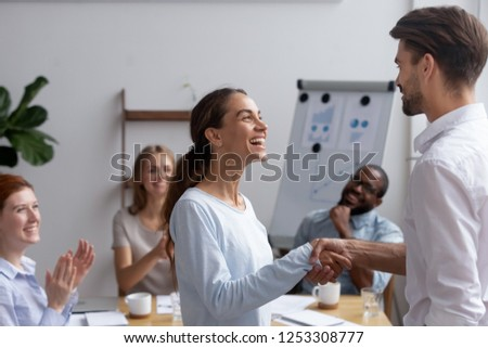 Excited mixed race girl employee get promotion feels happy handshaking with executive manager or company boss. Director greeting newcomer or congratulating successful worker with high rates at work #1253308777