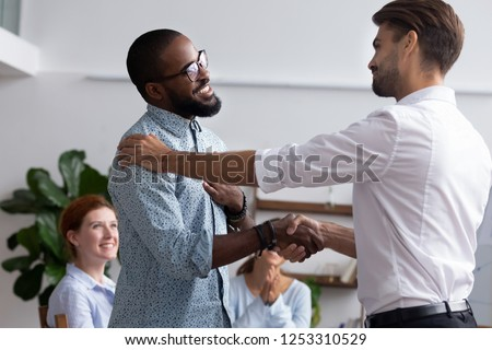 Diverse people gathered in meeting executive manager shake hands with black employee impressed by professionalism for leadership qualities creative solutions and efforts rewarding him for amazing work #1253310529