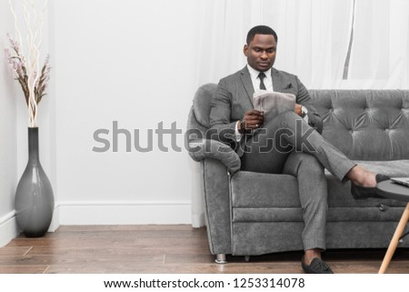 Young African American businessman in a gray suit reading a newspaper while sitting on a sofa. #1253314078