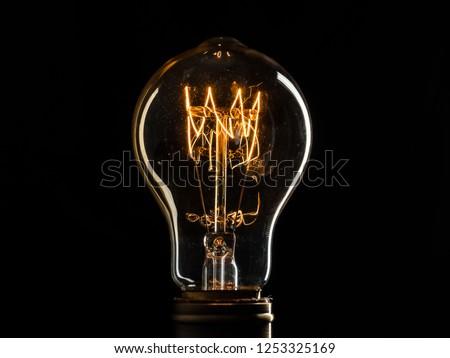Edison's light bulb illuminates from electric current #1253325169