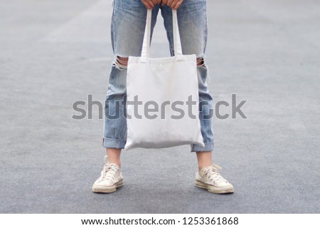 model hold blank white fabric tote bag for save environment on street fashion #1253361868