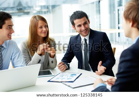 Image of business partners discussing documents and ideas at meeting #125338145