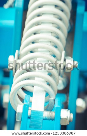 Steel spring as detail of agricultural machinery, part of hydraulic or pneumatic equipments, engineering and technology concept #1253386987