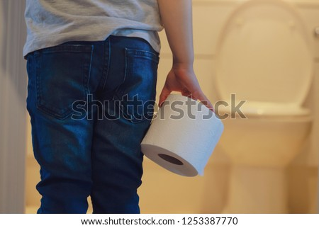 Rare view of kid holding toilet roll in the front of toilet, little boy suffers from diarrhoea holding toilet paper, Low view Child bringing roll of tissue walking to rest room, Children health care  #1253387770