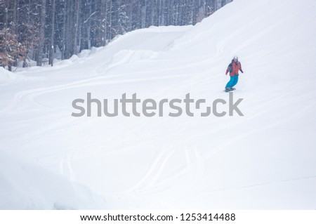 BUKOVEL,UKRAINE-19 MARCH,2018: Snowboarder athlete rides on board on specialized ski track in Bukovel Snow Park resort.Extreme winter sports in Southern Europe.Travel destination for holidays #1253414488