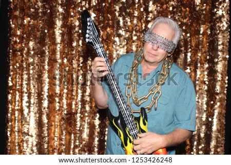 Photo Booth. A man smiles and poses with an inflatable Guitar in a Photo Booth. Photo Booth pictures.