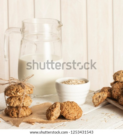 Oatmeal cookies with milk on tray on rustic wooden table #1253431543
