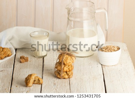 Oatmeal cookies with milk on tray on rustic wooden table #1253431705