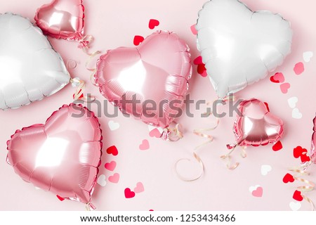 Air Balloons of heart shaped foil  on pastel pink background. Love concept. Holiday celebration. Valentine's Day or wedding/bachelorette party decoration. Metallic balloon #1253434366