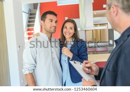 Happy couple talking to a state agent about buying the flat #1253460604