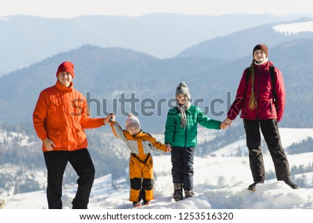 Mother, father and two sons are standing and smiling against the backdrop of snow-capped mountains. A happy family. Winter sunny day #1253516320