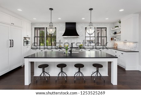 Beautiful Kitchen in New Luxury Home. Features Black Counters and Island, with White Woodwork and Cabinetry. Lights are Turned On. #1253525269