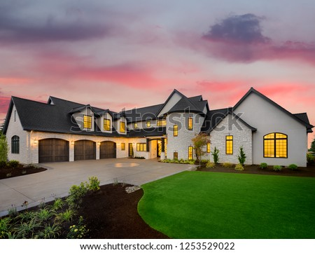 luxury home exterior: mansion with green yard and three car garage with glowing interior lights and sunset sky #1253529022