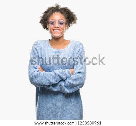 Young afro american woman wearing glasses over isolated background happy face smiling with crossed arms looking at the camera. Positive person. #1253580961