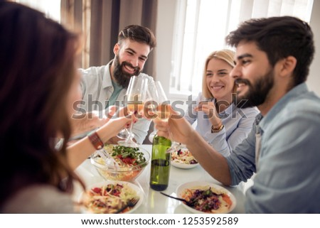 Leisure,eating, food and drinks, people and holidays concept - smiling friends having lunch and drinking wine at home. #1253592589