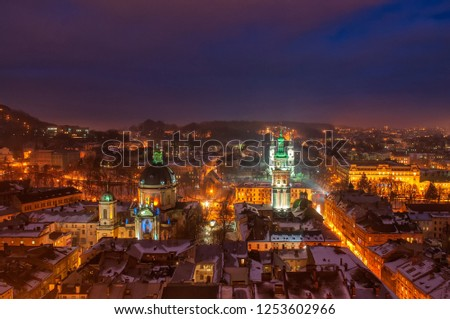 Aerial panoramic view of Dominican Monastery, Dormition Church, Korniakt Tower and old quarters in historical city center at night, Lviv, Ukraine. UNESCO world heritage site. Night winter cityscape. #1253602966