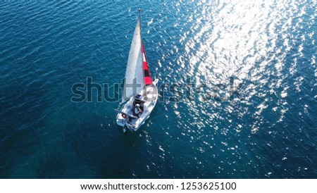 Aerial drone bird's eye view photo of small sail boat cruising in mediterranean open deep blue sea #1253625100