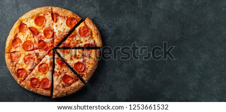 Tasty pepperoni pizza and cooking ingredients tomatoes basil on black concrete background. Top view of hot pepperoni pizza. With copy space for text. Flat lay. Banner #1253661532