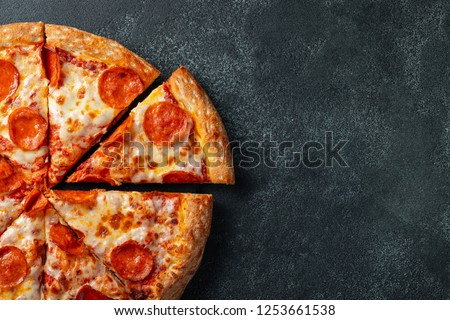 Tasty pepperoni pizza and cooking ingredients tomatoes basil on black concrete background. Top view of hot pepperoni pizza. With copy space for text. Flat lay #1253661538