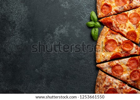Cut into slices delicious fresh pizza with sausage pepperoni and cheese on a dark background. Top view with copy space for text. Pizza on the black concrete table. flat lay #1253661550