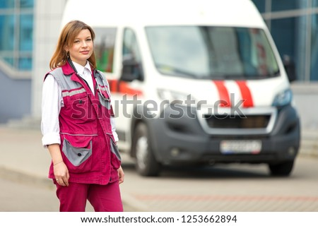 Young paramedic medical technician with phonendoscope at emergency car background #1253662894