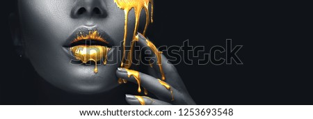 Gold Paint smudges drips from woman face, lips and hand, lipgloss dripping from sexy lips, golden liquid drops on beautiful model girl's mouth, gold metallic skin make-up. Beauty woman makeup close up #1253693548
