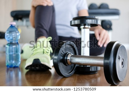 Woman exercise by personal trainer at gym and then be tired. She sit on floor for rest that dumbbell in front of her. Women wearing sport shoes. #1253780509