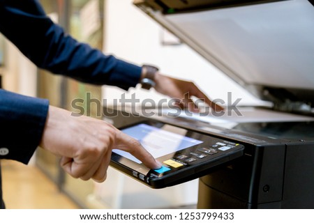 Bussiness man Hand press button on panel of printer, printer scanner laser office copy machine supplies start concept. #1253799433