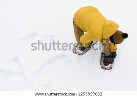 man on nature in winter wears a special device for walking in the snow #1253859082