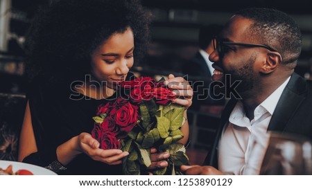 African American Couple Dating in Restaurant. Romantic Couple in Love Dating. Cutel Man and Girl in a Restaurant Making Order. Romantic Concept. Man Giving Bouquet of Flowers. Red Roses. #1253890129