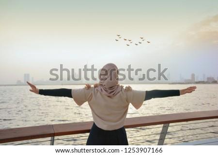 Happy arab woman look at dubai skyline, Dubai city view, wearing Abaya and Hijab #1253907166