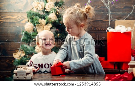 Cute little child near Christmas tree. Cheerful cute child opening a Christmas present. Christmas kids - happiness concept. Merry Christmas and Happy New year