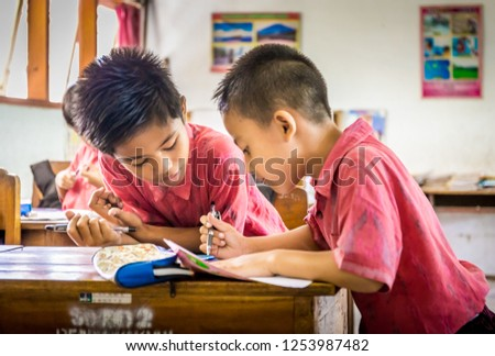 BALI, INDONESIA - APRIL 25, 2018: Young happy pupils wearing balinese school outfits studying at primary school on Bali island, Indonesia #1253987482