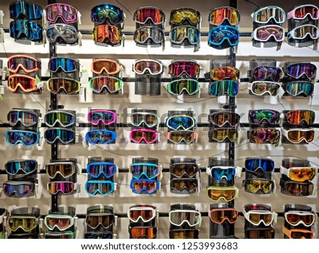 Sport equipment background. Colored snowboard masks in a rows on a showcase. Colorful ski masks on the shop window in the sports shop. #1253993683