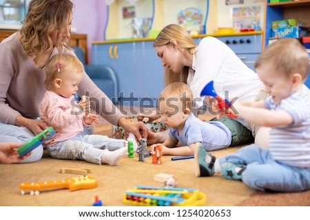 Friends with children toddlers playing on the floor in montessori centre #1254020653