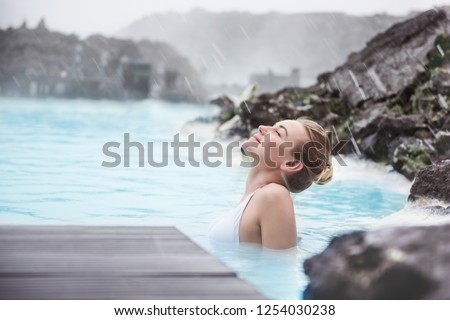 Woman enjoying natural spa, Blue Lagoon is a geothermal spa in southwestern Iceland, is located in a lava field near Grindavk on the Reykjanes Peninsula #1254030238