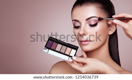 Makeup Artist applies Eye Shadow. Beautiful Woman Face. Perfect Makeup. Make-up detail. Beauty Girl with Perfect Skin. Nails and Manicure. Eye Shadow Palette #1254036739