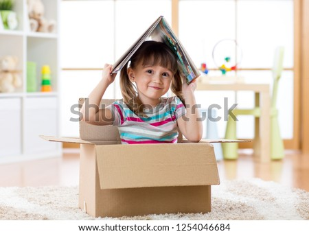 Smart kid girl sitting in cardboard box and holding a book over head as roof #1254046684