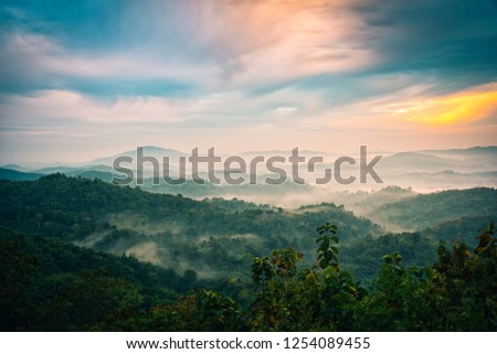 Foggy in the mountains with dramatic sky at sunrise #1254089455