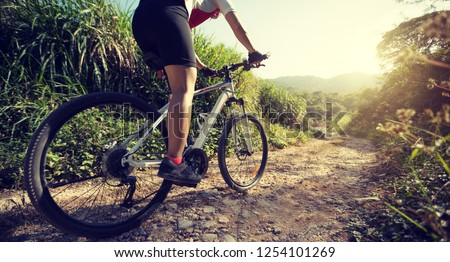 Woman cyclist riding a bike on a nature trail in the mountains.people living a healthy lifestyle #1254101269
