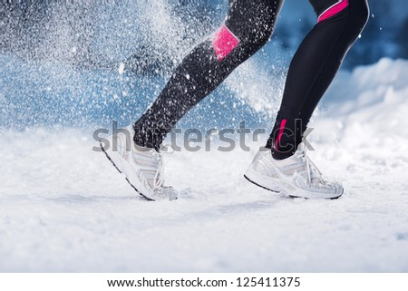 Athlete woman is running during winter training outside in cold snow weather. #125411375