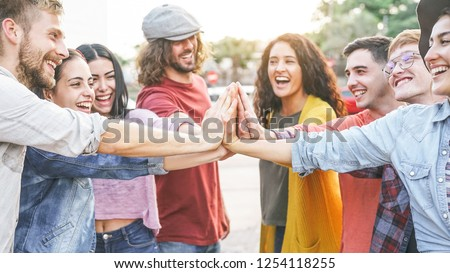 Group of diverse friends stacking hands outdoor - Happy young people having fun joining and celebrating together - Millennials, friendship, empowering, partnership and youth lifestyle concept  #1254118255