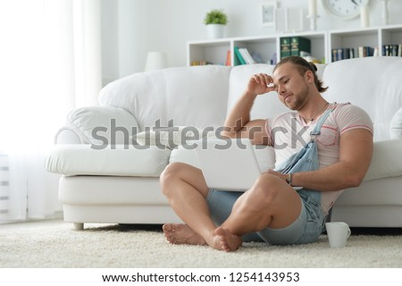Portrait of young hipster man spending time with laptop at home #1254143953