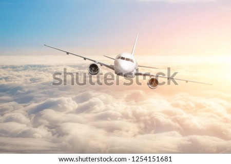 Passenger aircraft flying above the clouds horizon sky with bright sunset colors. #1254151681