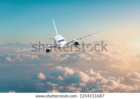 Passenger airplane flying above overcast clouds green pink gradient sky. #1254151687