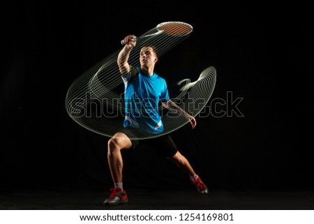 Young man playing badminton over neon black studio background. Fit male athlete isolated on dark with led light trail . badminton player in action, motion, movement. attack and defense concept